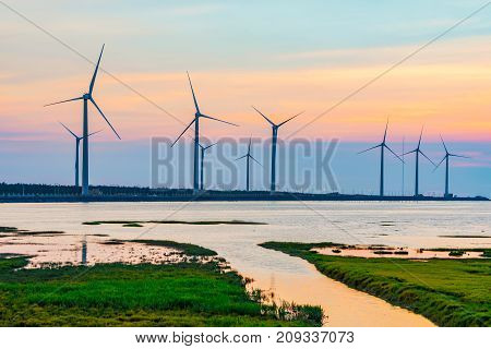 Scenic view of Gaomei wetlands wind turbines during sunset