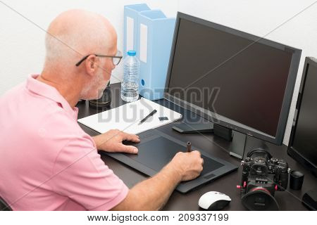 a mature man working with graphics tablet in his office