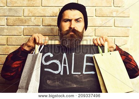 Bearded Hipster Holding Shopping Packages And Board With Sale Inscription