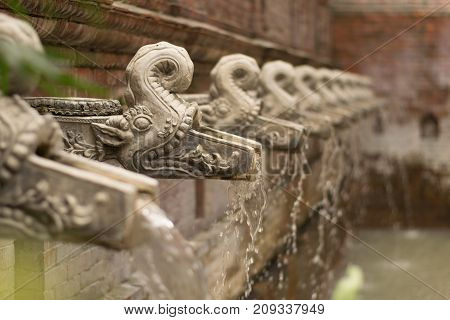 Traditional Nepali Water Taps Shaped Like Gargoyles, Filling A Swimming Pool In A Boutique Hotel, Ka