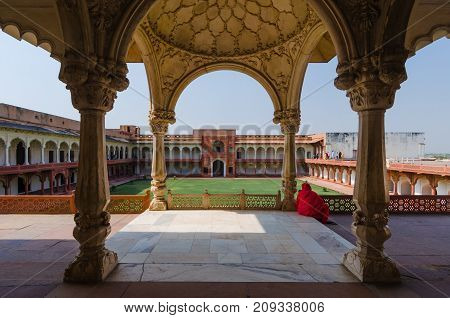 Agra, India - 4 May 2015: A Woman Drape Din A Red Saree Is Sitting Under The Loggia Facing The Jahan