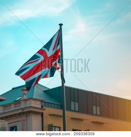 Great Britain flag on the pole in sunset