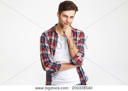 Portrait of a charming attractive man looking at camera isolated over white background