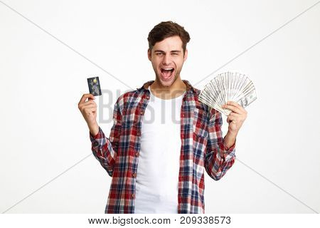Portrait of a happy excited man holding bunch of money banknotes with a credit card and screaming isolated over white background
