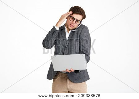 Portrait of a puzzled businessman in eyeglasses and a jacket holding laptop computer while standing and talking on mobile phone isolated over white background