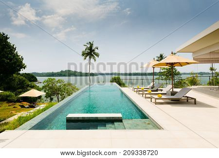 Infinity Swimming Pool Overlooking At A Lake, Bordered By Palm Trees, Lounge Chairs And Umbrella, In