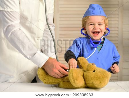 Health and childhood concept. Kid with happy face plays doctor. Male hand holds bear and boy in medical gown holds stethoscope on wooden background. Little assistant examines teddy bear
