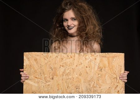 Beautiful girl with a gothic make-up as a witch smiles and holds a place for writing on a black background