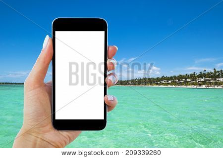 Beautiful woman's hand using smart phone at tropical beach. Near ocean. Smartphone isolated white screen. Blank empty screen. Empty space for text