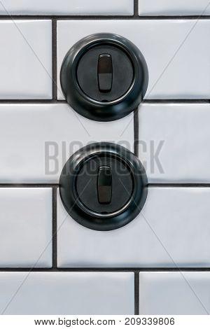 Two round black decorative bakelite light switches on white tile bathroom wall.