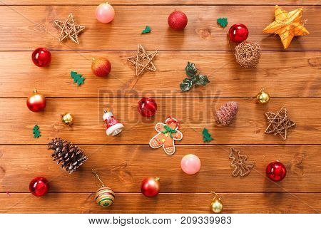 Christmas tree decorations background. Prepare for xmas eve or other winter holidays. Ornaments, tincel and garland concept background, top view on wood. Stars, gingerbread, pine cones and balls