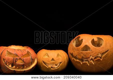 Three orange pumpkins with different faces for the holiday of Halloween on a black background