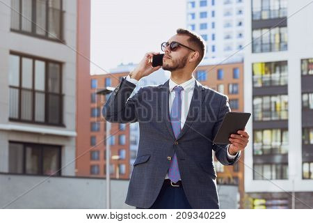 Real estate agent on background of modern city. Businessman is talking by mobile phone