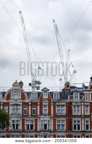 Two white cranes emerge against a cloudy sky and behind a row of typical brick houses in London UK.