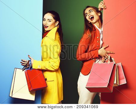 young sexy pretty funny women or model girls with long beautiful hair on happy face in colorful red and yellow coats with fashion makeup holding pegs on green blue studio background