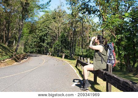 Beautiful woman hiker siting near forest trail and looking binoculars. Female with backpack on hike in nature. Travel Concept