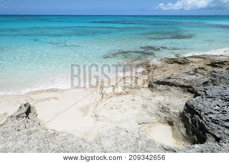 The rocky coastline and transparent waters of uninhabited island Half Moon Cay (Bahamas).
