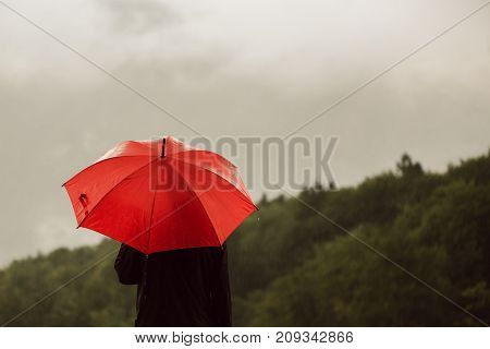 Man with red umbrella standing lonely in the rain and getting drenched