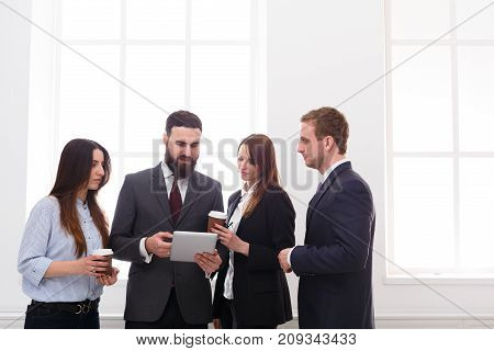 Managers meeting during coffee break. Corporate, success, brainstorming. Teamwork concept. Business people in light white office interior with windows, copy space