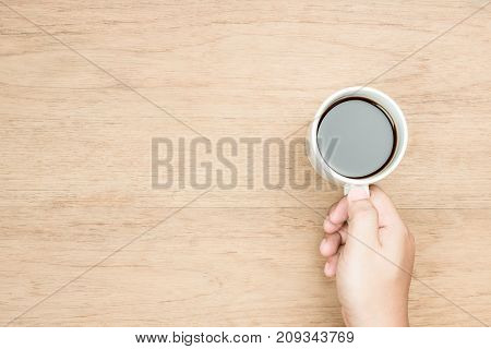 yellow brown skin tone hand holding white coffee cup wood texture from top view