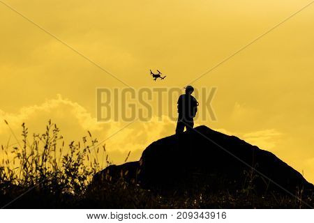 Silhouette of photographer with drone over the mountain tphotographer and ransportation concept
