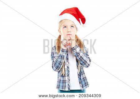 Portrait of sweet little girl in Santa hat blowing into party blower