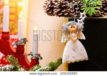 Christmas angel rag doll hanging on Christmas wreath with fir cones. Amid a festive candle holder with candles. Celebration of New year and Christmas at home