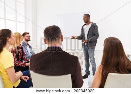 american man doing presentation in office, copy space. Startup business meeting, sharing new ideas to partners, teamwork concept