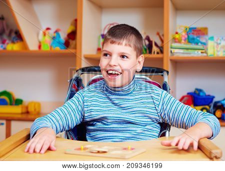 Cheerful Boy With Disability At Rehabilitation Center For Kids With Special Needs, Solving Logical P