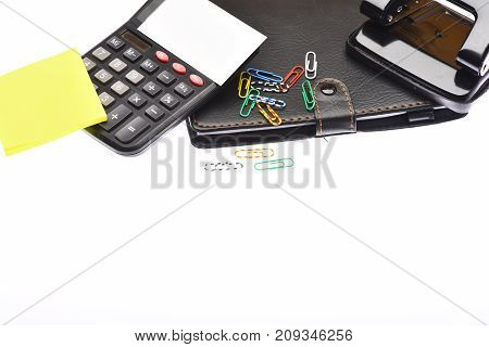 Business and work concept. Calculator and stationery with copy space. Office tools isolated on white background close up. Leather covered notebook hole punch card holder note paper and clips.