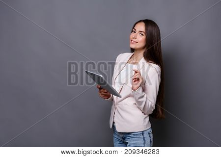 Business woman with digital device. Beautiful businesswoman at gray studio background with tablet, copy space