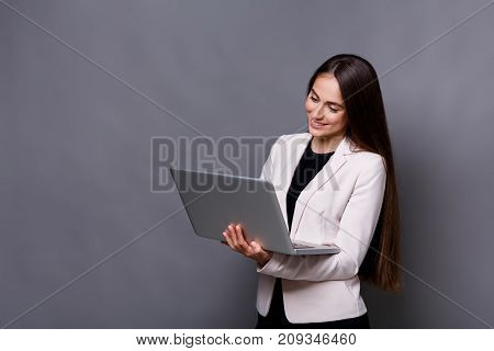 Smiled business woman using laptop on gray background. Communication concept, copy space