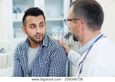 Sad young man listening to his doctor encourage after voicing diagnosis