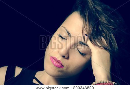 Close up portrait of beautiful young girl with closed eyes and leaned head to hand because she suffering from strong migraine headache pain attack - not isolated dark background