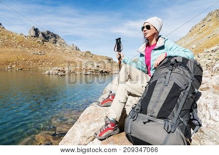 A tourist girl wearing sunglasses down jacket and hat with a backpack and mountain equipment with handles for tracking in her hands is sitting and relaxing looking at the beautiful view of the high mountain lake in the North Caucasus. Karachay-Cherkess Re
