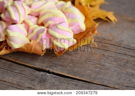 Yellow and pink mini marshmallows on yellow autumn leaves and on a vintage wooden background with copy space for text. Heap of sweet marshmallow closeup