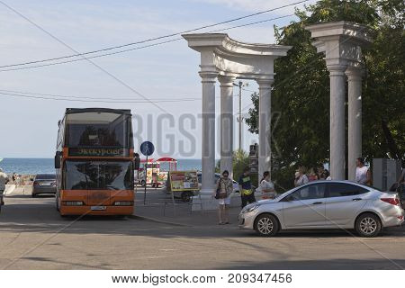 Evpatoria, Republic of Crimea, Russia - July 19, 2017: Group of tourists is going on a sightseeing trip on a double-decker bus-cabriolet