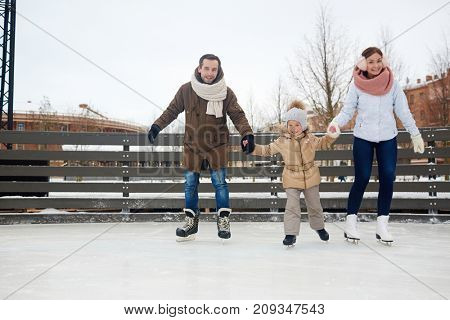 Happy couple and their daughter on skates moving down ice-rink in urban environment poster