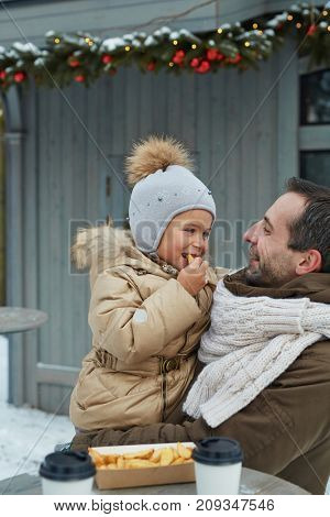 Affectionate father holding his adorable daughter eating snack on festive event outdoors