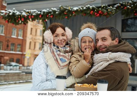 Hungry family eating french fries and having hot drinks outdoors