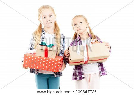 Little sisters posing with Christmas gifts on white background