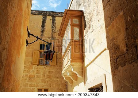 Building with traditional maltese balcony in historical part of Mdina.