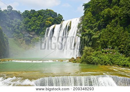 China Guizhou Huangguoshu Waterfall in Summer. One of the largest waterfalls in China and East Asia classified as a AAAAA scenic area by the China National Tourism Administration.