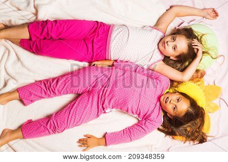 Kids In Pink Pajamas Have Fun. Children With Tired Faces