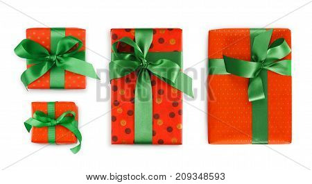 Four gift boxes wrapped in dotted red paper and green satin ribbon, isolated on white background. Modern present for any holiday, christmas, valentine or birthday