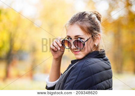 Young teenage girl with glasses standing in autumn park