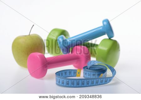 Apple And Green, Pink And Blue Barbells Near Measure Tape