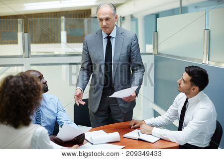 Group of brokers listening to report of their boss in office