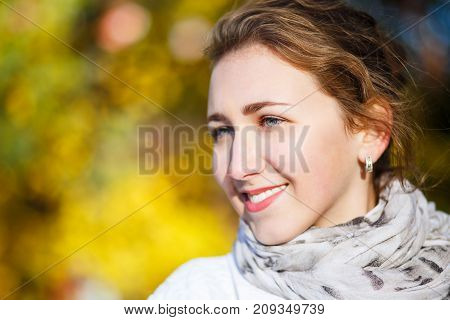 Young elegant woman in white coat standing in autumn park. Portrait of stylish girl in fall looking aside with copy space
