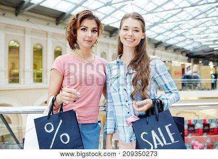 Young females with paperbags visiting shopping center during seasonal sale or on black friday